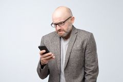 Dissatisfied man in casual suit wearing glasses reading articles, doing searching for information using phone. Dissatisfied, grouchy man in casual suit wearing stock photography