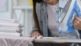 Dissatisfied housewife making hole in t-shirt during ironing, lack of experience. Stock footage stock video
