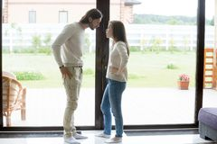 Dissatisfied husband and wife quarrelling at home. Dissatisfied husband and wife standing opposite panoramic window at home looking at each other with angry and stock image