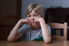 Dissatisfied kid sitting at table. Picture of dissatisfied small blonde kid sitting at table stock photo