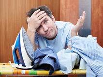 Dissatisfied man with pile of crumpled shirts and iron Stock Photo