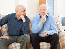 Dissatisfied men. Two dissatisfied men on couch stock images