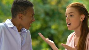 Dissatisfied multiracial young couple emotionally discussing relations in park