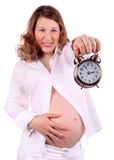 Dissatisfied pregnant woman holds at arm alarm clock Stock Photo