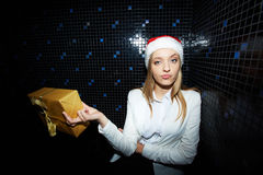 Dissatisfied with present. Dissatisfied businesswoman in Santa cap holding packed present stock images