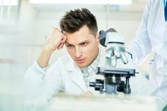 Dissatisfied Researcher at Modern Lab. Discontent young researcher wearing white coat sitting at laboratory bench and leaning head on hand while thinking over Stock Image
