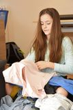 Dissatisfied teenage girl rummages in her outfit stock images