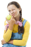 Dissatisfied teenager girl with apple Stock Photos