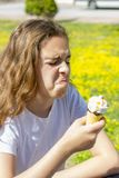 Dissatisfied unhappy teen girl eats tasteless ice cream in a waffle cone in summer. Selective focus. Dissatisfied unhappy teen girl eats tasteless ice cream in royalty free stock images