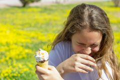 Dissatisfied unhappy teen girl eats tasteless ice cream in a waffle cone in summer. Selective focus. Dissatisfied unhappy teen girl eats tasteless ice cream in royalty free stock photos