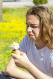 Dissatisfied unhappy teen girl eats tasteless ice cream in a waffle cone in summer. Selective focus. Dissatisfied unhappy teen girl eats tasteless ice cream in royalty free stock image