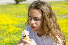 Dissatisfied unhappy teen girl eats tasteless ice cream in a waffle cone in summer. Selective focus. Dissatisfied unhappy teen girl eats tasteless ice cream in stock photo