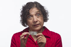 Dissatisfied woman holds dollar bill, horizontal. Older woman holding her nest egg, horizontal Stock Photography