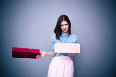 Dissatisfied woman opening gift. Over gray background stock image
