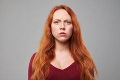 Dissatisfied woman with red hair over gray background Stock Image