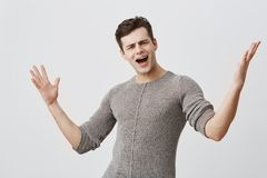 Dissatisfied young male with dark hair closes eyes and screams loudly, gestures, being very emotional after passing exam. Isolated against gray background Royalty Free Stock Photo