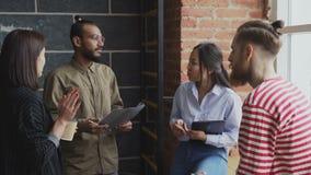 disscussing起始的项目的小组年轻不同种族的同事,当一起站立在窗口附近在现代办公室时 影视素材