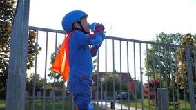 Dissetante, il bambino con il recipiente di plastica in armi beve l'acqua minerale su aria aperta