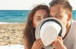 Dissimulation heureuse de jeunes couples derrière le chapeau Images libres de droits