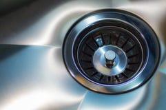 Dissipador de aço inoxidável com dreno closeup Um dreno de banca da cozinha de aço inoxidável foto de stock