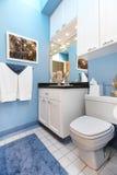Dissipador e toalete pequenos brancos do banheiro do wnad azul. Fotos de Stock Royalty Free