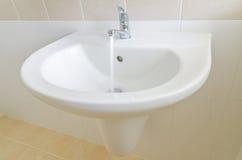 Dissipador e torneira brancos em um banheiro Fotografia de Stock
