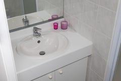 Dissipador mínimo limpo branco em um banheiro Imagens de Stock
