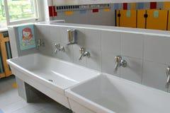 Dissipadores e bacias com as baixas torneiras nos toaletes de um berçário imagens de stock
