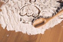 Dissipando sulla farina e sul cucchiaio della torta Fotografia Stock