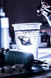 Dissolving tattoo ink in glass of water Royalty Free Stock Photography