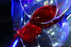 The bottled wine. The fallen glass. Dissonance. The bottled wine. The fallen glass. Blue color and red wine. Incongruous, unsuitable colors Royalty Free Stock Photos