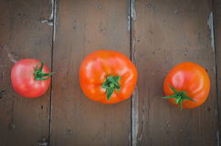 At distance from each other three tomatoes. On a wooden table Stock Photography