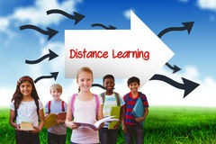 Distance learning against blue sky over green field. The word distance learning and smiling little school kids in school corridor against blue sky over green Royalty Free Stock Photos