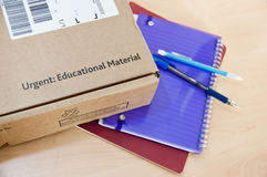 Distance learning delivery. High angle shot of distance learning cardboard box with notebooks underneath Stock Image