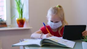Distance learning online education. Sickness schoolgirl in medical mask studying at home with digital tablet in hand and