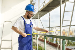 Distance measurement. Work on site, Worker at high altitude on scaffolding. Stock Images