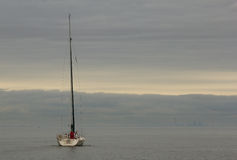 In the distance. Sail boat in Lake Ontario with Toronto in the distance royalty free stock photography