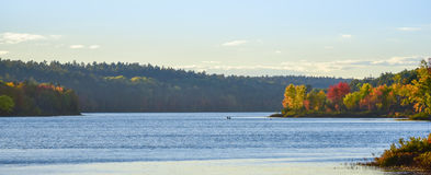 In the distance, two people in a boat.  Late summer afternoon, sun shines golden light on a lake. Stock Photo