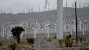 The distance video of operating windmills with massive mountains on the background stock video