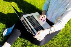Distancia de funcionamiento experta del blogger de la muchacha del inconformista en el cuaderno, descansando al aire libre fotos de archivo libres de regalías