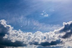 Distant backlit cumulus and feather clouds near horizon closeup telephoto shot with polarizing effect. Distant backlit cumulus and feather clouds near horizon royalty free stock photo