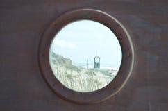 Distant beach scene. Distand beach scene viewed through a round window Stock Image