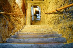 Distant blurred image of person near top of old stone stairway i. N golden low light with round wooden handrails up each side royalty free stock image