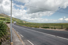 Distant bus on the road in sunny day. Irish rural scene with distant bus on the road on summer sunny day Stock Photos