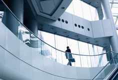 Distant businessman walking in a modern office building Stock Photos