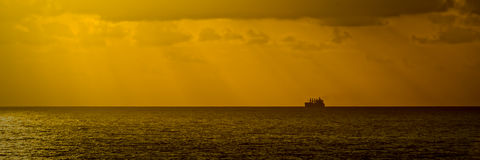 Distant Cargo Ship on the Horizon. A photo of a cargo ship sailing on the open sea  and seen sitting on the horizon silhouetted against the orange sky in the Royalty Free Stock Image