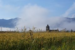 Distant church over field. Fog burns off in the morning hours as a church becomes visible over a field of wheat with mountains in the background Royalty Free Stock Photo