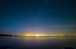 Distant City Lights With Stars and Water Royalty Free Stock Photos