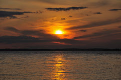 Distant cloudy sunset over huge lake. The final stage of a cloudy sunset above the huge lake in Karelia region. The picture is colorful and relaxing royalty free stock photos