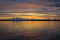 Distant colorful sunset. The final stage of a cloudy sunset above the huge lake in Karelia region. The picture is colorful and relaxing stock photos